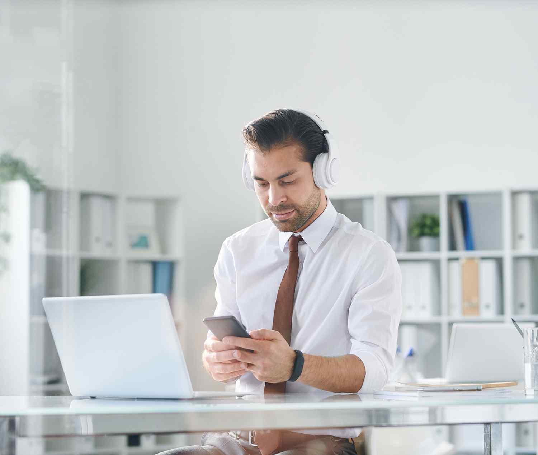 young elegant man in headphones scrolling in smart SPXKMZU